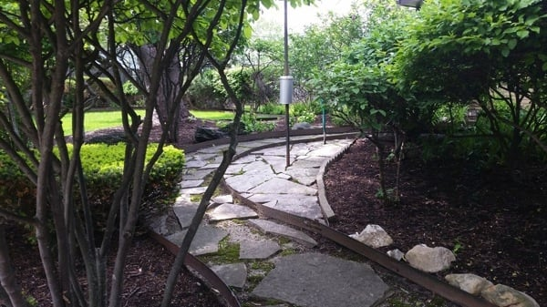 Poul's Landscaping & Nursery creates a park-like setting in this yard with curved flagstone pathways, and an assortment of plants and bushes. (Photo courtesy of Angie's List member Alice R. of Gurnee, Ill.)