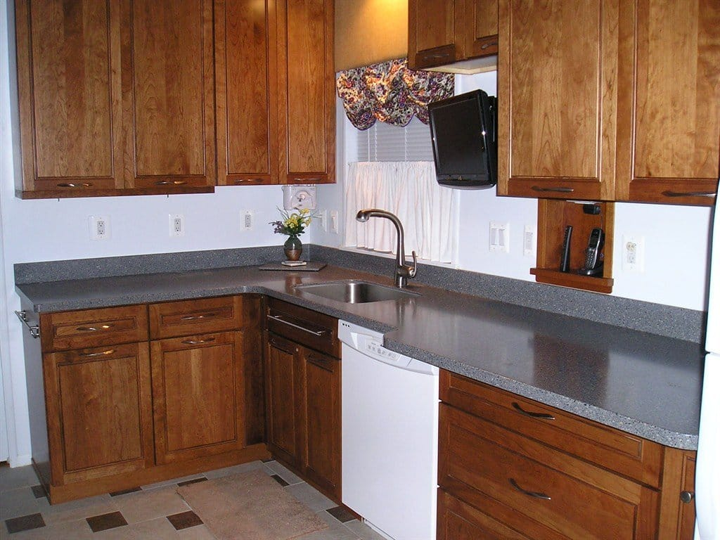 L-shaped corian countertop on cherry cabinets