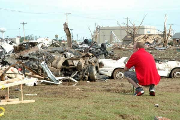 A young man stops and reflects at the site where lives were lost during Monday's tornado. (Photo by Katie Jacewicz)