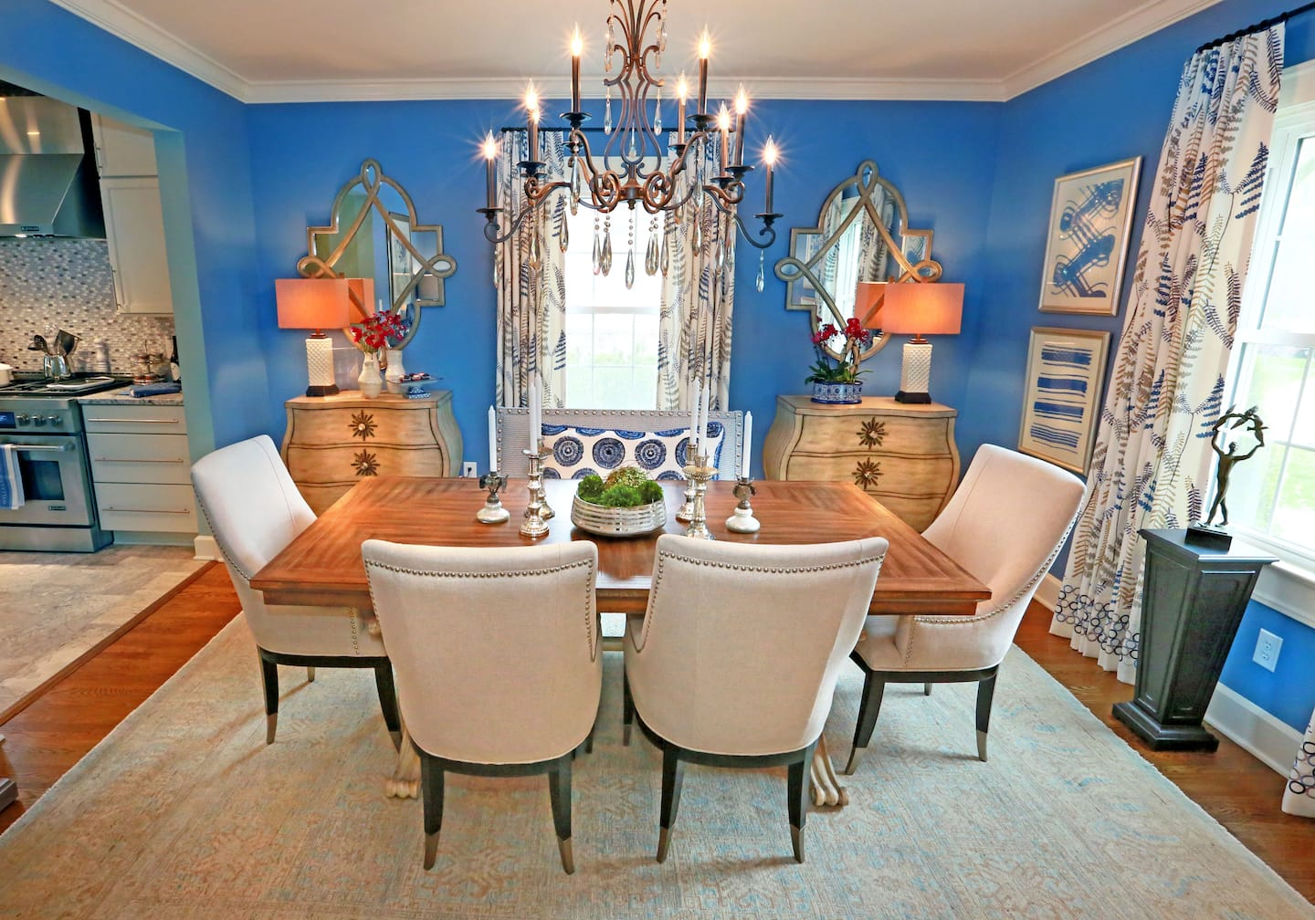 Eclectic Formal Dining Room With Patterned Drapes Decorative Mirrors Artwork And Traditional Chandelier