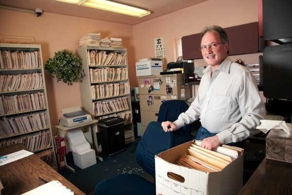Dr. Gerald Roth packs boxes at Madera Medical Clinic in Tucson, Ariz. in preparation to close the practice. He joined Northwest Allied Phyisicians in September. (Photo by Al Mida)