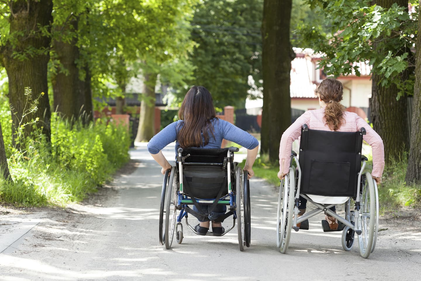 two young girls using wheelchairs on path