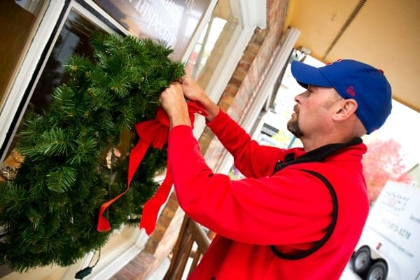 hanging a Christmas wreath in downtown Zionsville (Photo by )