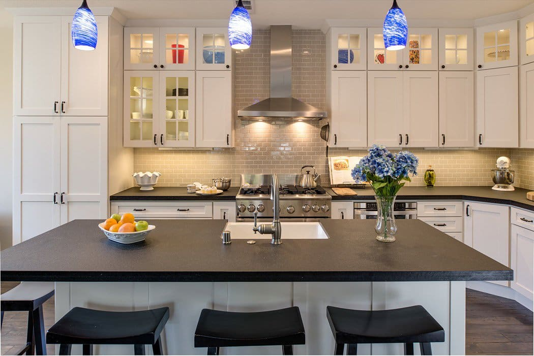 Remodeled kitchen with in-cabinet lighting, under-cabinet lighting and three pendant lights with art glass shades over the island