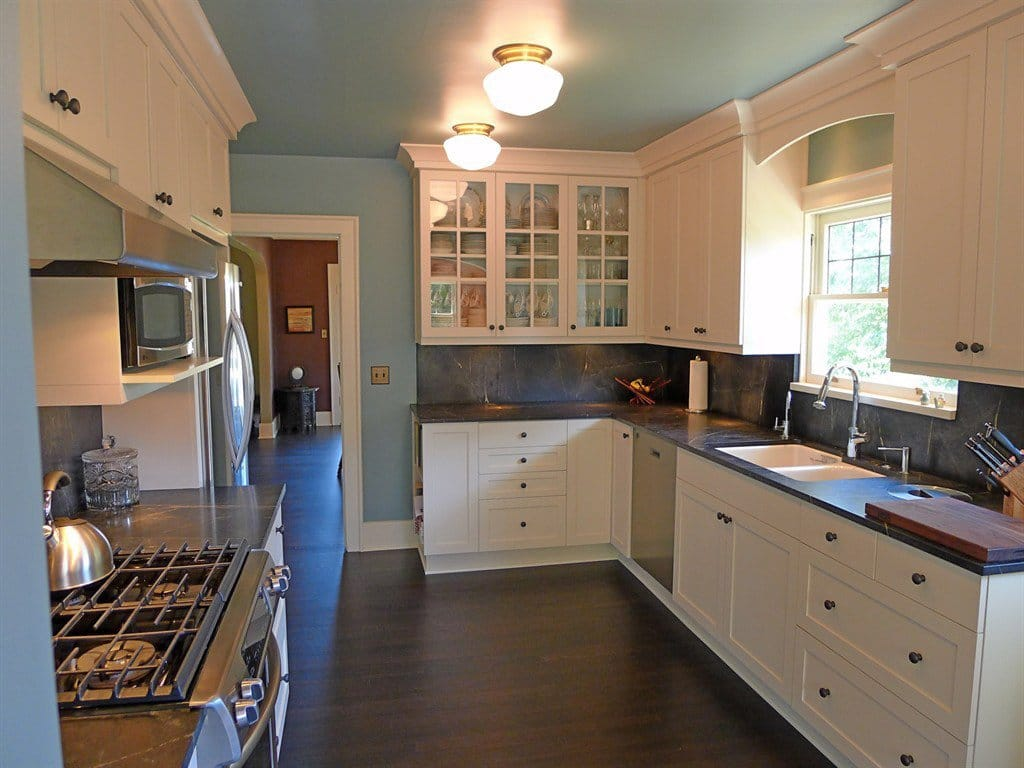 White kitchen cabinets topped with dark soapstone countertops