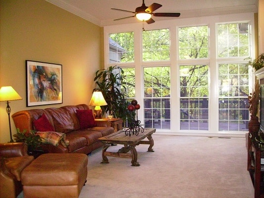A staged living room with light brown leather furniture, white carpet, and white french doors.