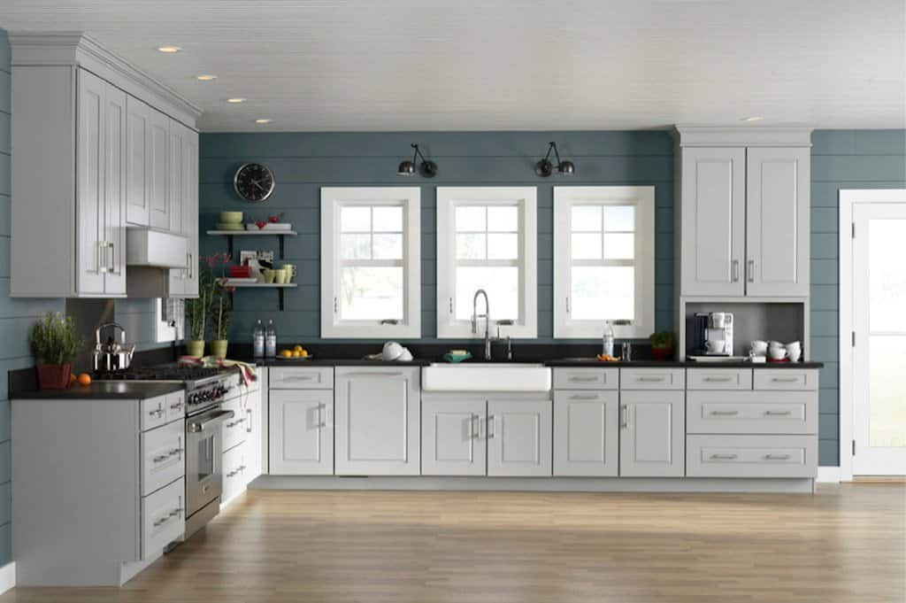 White cabinet with black countertops and teal painted walls