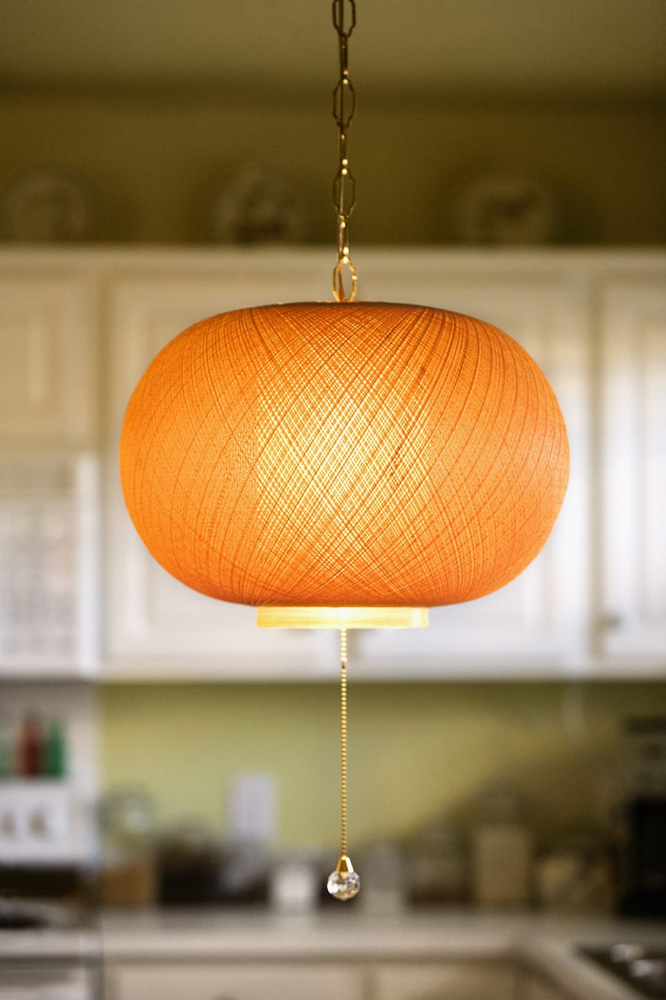 An orange woven light fixture hanging from the ceiling