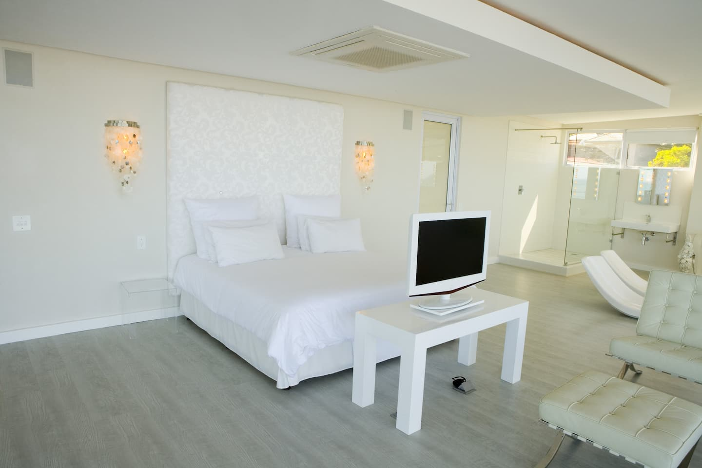A bright white bedroom with retro-styled sconces on the wall on either side of the bed.