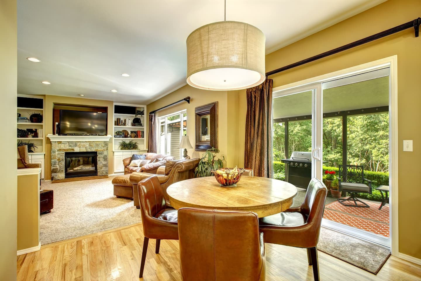 A tan-colored dining room with a family room in the background