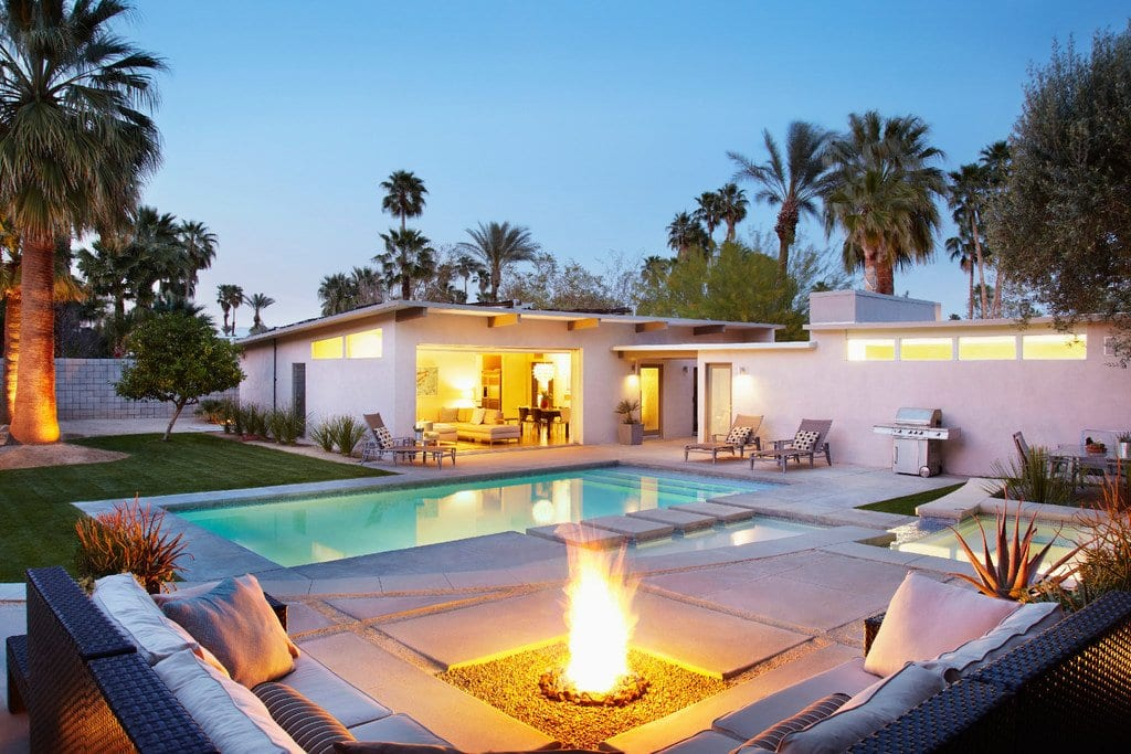 Pool with spa areas and fire pit with couch