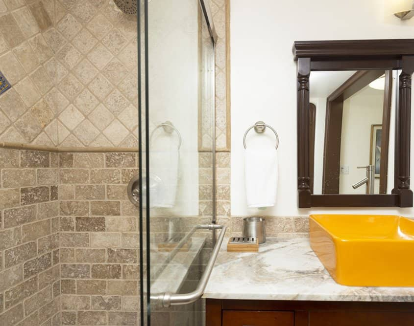 Travertine tile shower and marble countertop in bathroom