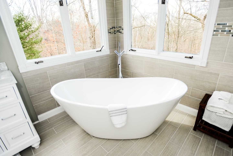 Large soaking bathtub shaped like basin inside bathroom
