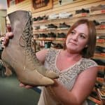 Mary Coffman at Eckstein's Shoes holding a pair of boots