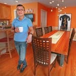 man with coffee cup in orange dining room