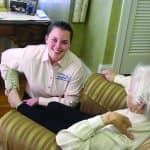 caregiver assisting elderly woman in home