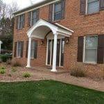 Colonial portico porch anchored by white column pillars