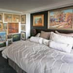 master bedroom with wall of artwork
