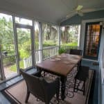 screened-in back porch with table and chairs