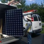 a solar panel installer pulling some out of a van