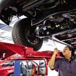 a mechanic looking at the undercarriage of a car
