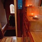 Candles and sensor lights on whood staircase drawers light narrow entryway.