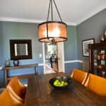 Eclectic contemporary dining room with modern lantern-like chandelier, rustic farmhouse-style table and dark wood curio cabinet with mid-century modern glassware