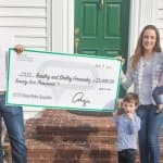 husband and wife with two small children holding big check in front of home