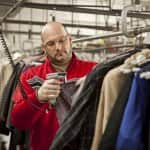 man scans clothing tag at a dry cleaner