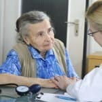 An elderly patient talks with a female doctor