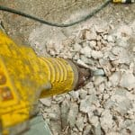 jackhammer busts up concrete foundation