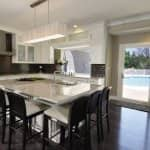 white kitchen with glass cabinet doors and granite kitchen island.