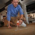 man spraying cleaner on carpet