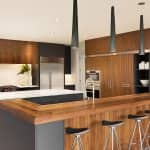 kitchen island with wood, gray cabinets, pendant lighting