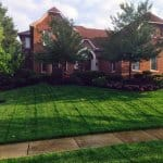 brick home with lush green lawn being watered