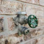 blue handled outdoor faucet on a brick wall