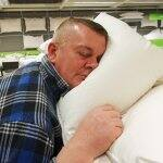 A man tests out a pillow at a store display