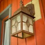 frosted glass porch light framed in brass and accented with clear glass diamond in the center