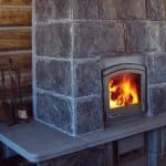 Stone wood cabin fireplace with soapstone waist high counter