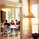 A group of people eating a meal around a table with a unique light fixture overhead
