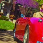 red convertible with woman driving and scarf flying