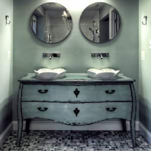light green repurposed dresser with drawers and vessel sinks on top
