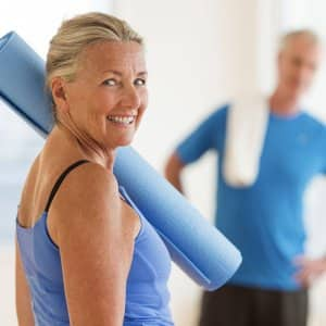 A smiling woman has a rolled up excercise mat over her should while a man stands in the background