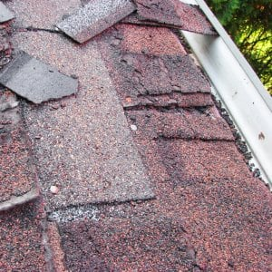 two layers of crumbling asphalt shingles