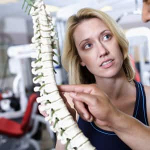 A doctor shows a woman a model of a spine