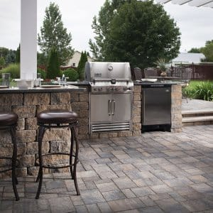 Outdoor kitchen with stainless steel grill, bar and stone patio