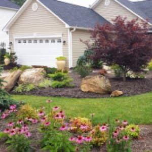 Home with landscaping featuring boulders, evergreens and flowers. (Photo by Photo courtesy of Lawn-N-Order Landscaping)