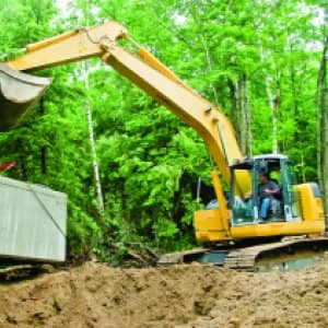 Installing Septic Tank With Excavator At Construction Site. (Photo By  Jupiterimages )