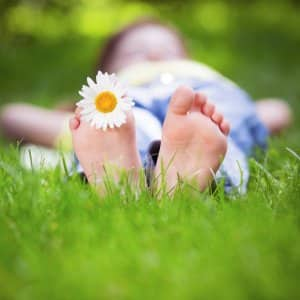 laying in grass, flower in toes