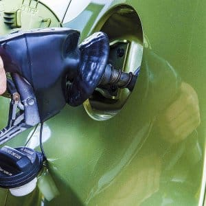 pumping gas in green car